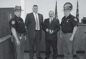 Perry County officials examine a new X26 Taser that will be used by the Perry County Probation Department. Oglebay Norton Industrial Sands Inc. of Glenford donated $1,000 for the purchase of the new unit. From left to right: Deputy Shane Patterson, X26 trainer for the sheriff's office;Probation officerBrad Agriesti; Judge Dean L. Wilson; and Sheriff William R. Barker. Courtesy photo.