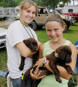 Leanne Butts (left) and Kelsey Hoar enjoy some puppy love.