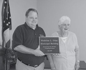 More than 50 friends and relatives turned out last Saturday morning for the dedication of the Millersport Municipal Building to Madeline L. Utley. Above, Millersport Mayor Dean Severance holds the bronze plaque that will be attached to the building, honoring Utley for more than 40 years of service as clerk/treasurer to the residents of Millersport. She retired from village service on May 31. A reception was held after the ceremony. Beacon photo by Scott Rawdon.