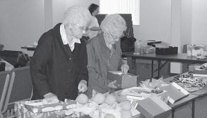 Two members of the Joy Bible Class at the First Community Church of Buckeye Lake pack gift shoeboxes for Operation Christmas Child, a ministry of Samaritan's Purse. Operation Christmas Child sends shoebox gifts to millions of children around the world, from war torn countries to areas hit by natural disasters. Shoeboxes are assembled for boys and girls and in three age ranges -  two to four years, fiveto nine and 10 - 14. Each shoebox contains a variety of items, including toys, hygiene products, hard candies and gum and school supplies. First Community is serving as a Relay Center again this year, accepting fillshoebox gifts Nov. 12 - 18. Collection hours are: Monday, Nov. 12 thru Friday, Nov. 16 - 5 - 8 p.m.; Saturday Nov. 17 - 10 a.m. to 5 p.m.; and Sunday, Nov. 18 - 1 p.m. to 3 p.m. Last year the Joy Bible Class filled 400 shoeboxes. Boxes should not include used or damaged items; anything war-related like toy guns, knives or military figures; chocolates or food; liquids or lotions, medications or vitamins, breakable items; or aerosol cans. Cash donations of $5 or more per box are sought to help cover shipping and other costs. More information about Operation Christmas Child is available at www. samaritanspurse.org or from Kellie at First Community Church, (740) 522-9183. Beacon photo by Charles Prince.