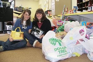 Millersport High School seniors Cecilia Knox (left) and Brandi Colley sit among a roomful of toys, gifts, and food items collected as part of the Walnut Township School District's 37th annual White Christmas program.