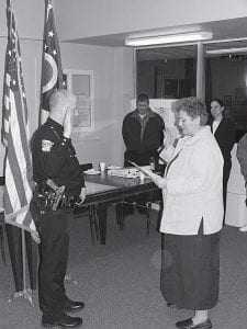 Thornville Mayor Beth Patrick administers the oath of officeto Police Chief Nick Garver Tuesday night. Beacon photo by Charles Prince.