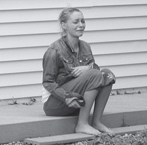 Tanya Hager grieves outside of Raymond Dymek's Shepard Avenue home Friday afternoon in Walnut Township. Earlier, Dymek shot and killed her father, Hayden