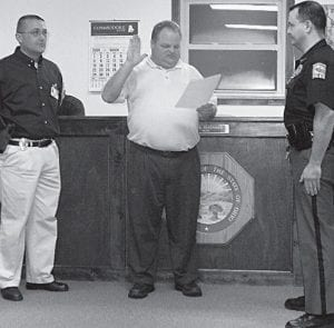 Millersport Police Chief Randall Lewis, left, looks on as Mayor Dean Severance swears in part-time paid Police Officer Mark Consolo. He had previously been an unpaid reserve officer. Consolo will be paid $10 per hour for up to 24 hours per week. His addition gives the village two parttime paid officers plus the full-time chief. Courtesy photo.