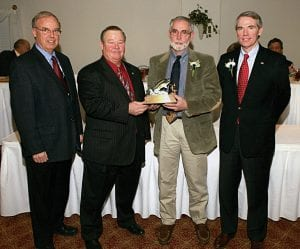 The League of Ohio Sportsmen named Tim Mason of The Dawes Arboretum Water Conservationist of the Year at its Annual Conservation Awards Banquet in Marietta. Mason was cited for his promotion and education of the public on the value of wetlands in Ohio and his dedication in the promotion of wildlife habitat. Above, League President Larry Mitchell presents Mason with a Black Bass statuetee as keynote speaker and former U.S. Congressman Rob Portman, right, and League Vice President Dan Olszak congratulate Mason. The League of Ohio Sportsmen' mission is