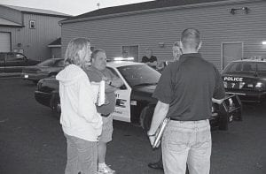 Millersport Police Captain John Shirk, partially obstructed, explains the new cruisers' features to Carol and Chris Tennant as Millersport Mayor Dean Severance listens. The village purchased three- fully equipped 2006 Ford Crown Victoria cruisers from the City of Gahanna for a total of $12,000. Beacon photo by Charles Prince.
