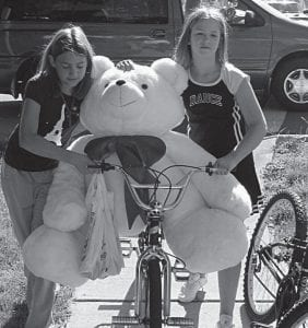 Two Hebron girls, Tasia Susi on the left and Zoie Mason, take their $4 bargain bear home Saturday. Upper right, US 40 in Hebron was jammed with yard sales and shoppers Saturday. Beacon photos by Charles Prince.