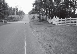 Licking Township resident Robert Snedden Sr. has removed the stumps, rocks, railroad ties and excess vegetation from along the roadway at 8051 Somerset Road. Trustees had declared the area a nuisance, giving him seven days to clean it up. The white line represents Snedden's calculation of where the eastern edge of the roadway should be. Courtesy photo.