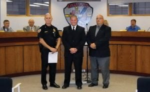 New auxiliary Police Officer James Farmer is flanked by Police Chief James Dean, left, and Mayor Clifford L. Mason.