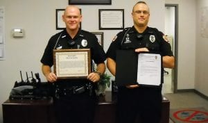 Police Officers Travis Shanaberg, left, and Chris Redmond display their service awards. Courtesy photos.