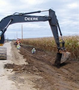 A Shelly Company crew checks the slope of a new drainage ditch on the east side of Cherry Lane in Walnut Township. Work started about two weeks ago on the first phase to rebuild the township's narrowest road. The project will widen the road from its current 12 - 14 feet to a consistent 18 feet, add two-foot berms on each side, move fences back to the edge of the 60 foot right-of-way and construct new ditches. Utility poles have been moved to the east side and placed on the edge of the right-of-way. This phase runs from Blacklick Road north to the Licking County line. The Shelly Company was the low bidder at $294,261.10, which was considerably lower than the $348,079 estimate. Walnut Township's share is $73,565 with the balance being paid by an Ohio Public Works Commission grant. Walnut and Liberty townships jointly own the road. Walnut Township takes care of the northern portion where it is being rebuilt, while Liberty is responsible for the southern portion. Liberty Township is not contributing to the project. Work should be completed by Thanksgiving. Walnut Township is seeking an additional OPWC grant to fund most of the cost for phase two which runs from Blacklick Road south to Ohio 204. Beacon photo by Charles Prince.
