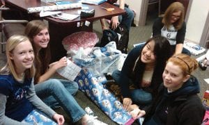 Lakewood High School's annual Adopt a Family fund raiser raised $700 for area children. In total Lakewood High School was able to purchase gifts for 30 children that live within our school district due to the generous donations of toys and money from students and staff members. Pictured are student council members wrapping presents to be delivered to Hebron Elementary School. From right to left, Lauren French, Brittany Henry, Yves Amornyard, Haily Chandler, and Heather Coffman. Courtesy photo.