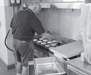 Vince Popo handles the pancakes as school board members serve breakfast to staff members on their first day back from summer vacation. Beacon photo by Charles Prince.