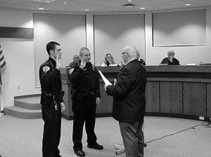 Hebron Mayor Clifford L. Mason administers the oath of office to part-time Officer Anthony, left, and full-time Officer James Farmer. Beacon photo by Charles Prince.