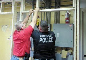 Millersport Police Chief John Shirk (red shirt) and Officer Dustin Hardway (black shirt) work to convert the former Millersport water treatment plant into a new police station.