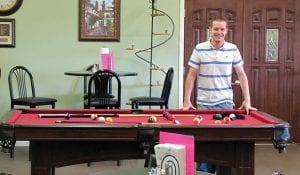 Pastor Jacob Foulk checks out the pool table at the New Life Cafe in Buckeye Lake. Beacon photo by Scott Rawdon.