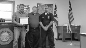 Millersport Mayor Dean Severance, center, and Police Chief Mark Consolo presented John Hitchcock with a Certificate of Heroism for chasing down a burglary suspect at 3 a.m. on Aug. 28. The suspect had entered the Severance's parents' home and taken his mother's purse and some medications. Beacon photo by Charles Prince.