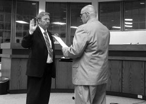 Hebron Mayor Clifford Mason administers the oath of office to Ralph C. Wise. He starts as village administrator on Oct. 1. Beacon photo by Charles Prince.