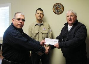 """Hebron Fire Department received a $4,800 First Responder Grant from Marathon Petroleum Company last week. Hebron Fire Chief Randy Weekly, right, said it would be used toward specialized equipment to help remove accident victims trapped in commercial vehicles and machinery. It would be available to departments via mutual aid. Marathon transport driver Duane Moore, left and formerThorn Township Fire Chief, said trucks containing hazardous materials often pass though the greater Hebron area, including Marathon Oil trucks. """"We go through here a lot,"""" he said. Moore presented the $4,800 check to Weekly with Marathon Regional Transport Manager Chris Lint. Beacon photo by Scott Rawdon."""