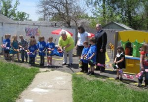 Melissa Shaw, Head Start health and disabilities manager, cut the ribbon on the new expanded Head Start playground behind the Buckeye Lake Food Pantry Wednesday. Licking County Foundation Director Connie Hawk and LEADS CEO Kenneth Kempton joined watched. Beacon photos by Scott Rawdon.