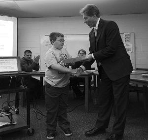 Walnut Township Local Schools Superintendent Randy Cotner presents third grader Tyler Large with an Anchor Award for his $34 contribution toward the district's deficit. Courtesy photo.
