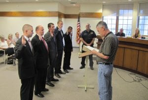 "Hebron Council President Bob Gilbert recently administered the oath of office to five new part-time firefighters/EMTs. From left to right are Jacob Gates, Brad Essick, Ryan Crabill, Zachery Petty and Taylor Smith. Brian Neighbor was sworn in the next day. Essick, Smith and Neighbor are paramedics; the others are EMT's. Fire Chief Jack Stickradt, center, called the group ""the cream of the crop."" Beacon photo by Charles Prince."