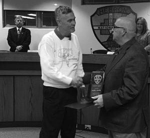 Retiring Council President Bob Gilbert, left, gives Mayor Clifford Mason a plaque for his 35 years of service to the village. Beacon photo by Charles Prince.