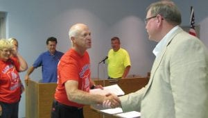 Buckeye Lake Village Mayor Clay Carroll, right, gives head Lakewood softball coach Criss Nadolson a copy of the proclamation honoring the 2016 Division II state champions. His wife, Joyce Nadolson, who serves as scorekeeper and team mother, waits for her proclamation as council members Tim Rayn ad Tom Wolfe watch. Beacon photo by Scott