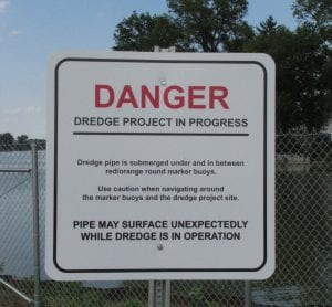 """More detailed dredge warning signs were recently placed at Buckeye Lake boat ramps. The new sign, at left above, warns that the dredge discharge pipe is submerged, but may """"surface unexpectedly while dredge is in operation."""" The sign also says the discharge line is marked with red/orange round buoys. At right is what a boater encountered on June 13 heading north between Onion Island on the right and Lieb's Island on the left. The horizontal crease about halfway up the photo is the discharge line floating just below the surface. While the boater was aware of dredging activities in the general area, there were no buoys on this portion of the line between these two islands. The boater only noticed the barely submerged pipe after a seagull landed on it. More buoys have reportedly been placed since last week, but boaters should be particularly cautious around dredges and watch closely for the discharge lines."""