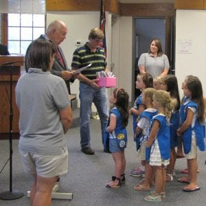 Hebron Mayor Mike McFarland, second from left, reads a Certificate of Appreciation to the leaders and members of Daisy Troop 7509 at the July 26, Village Council meeting. Council member Tom Marietta, third from left, helped McFarland distribute a certificate to each troop member. Troop leaders asked for a community project so the scouts cleaned up trash that accumulates against a fence on the eastern end of the Kroger store parking lot. Beacon photo by Charles Prince.