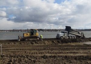 A dozer pulls out a dump truck that got stuck dumping bank run into Buckeye Lake to build the new causeway around the AMIL Spillway.