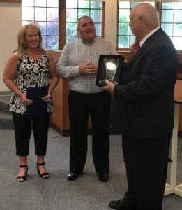 Hebron Mayor Mike McFarland presents a plaque to retired Hebron Fire Captain Rich Vance in honor of his 28 years of service to the village. McFarland also thanked Vance's wife for her patience with his service. Courtesy photo.